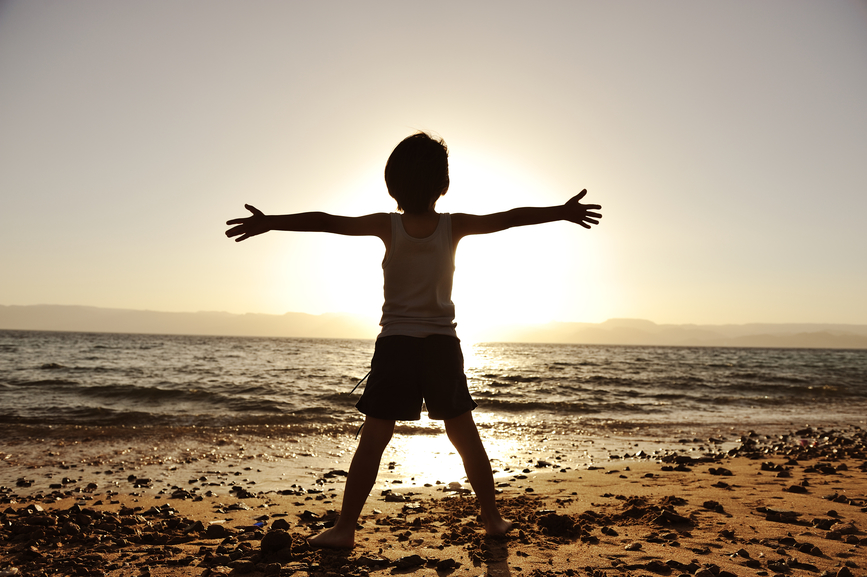 Silhouette of child on the beach, holding his hands up, towards the sun